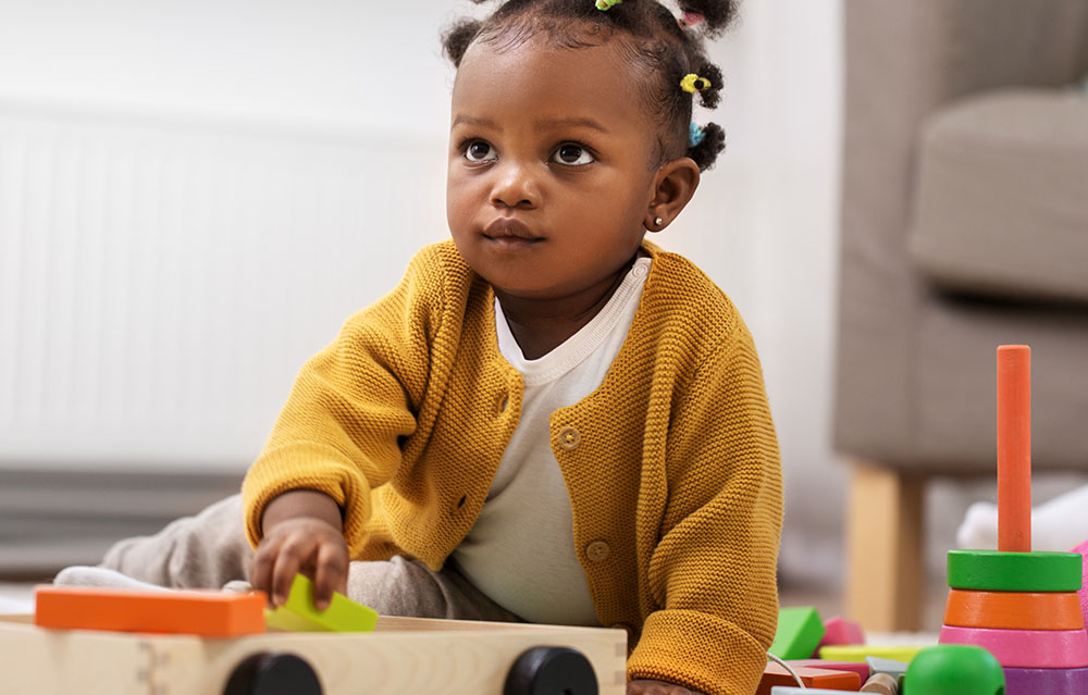 focused baby girl playing with toys at a Preschool & Daycare Childcare Center serving Conway & Myrtle Beach, SC.